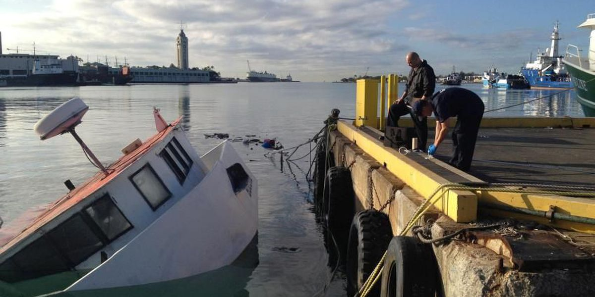 Army divers in process of removing sunken fishing vessel from Honolulu Harbor