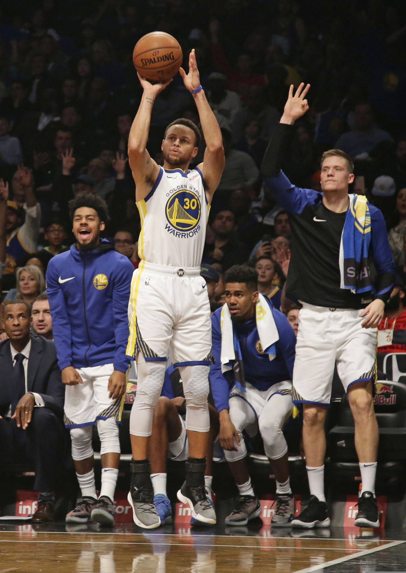 c88717af670f Golden State Warriors react as teammate Stephen Curry shoots a three-point basket  during the