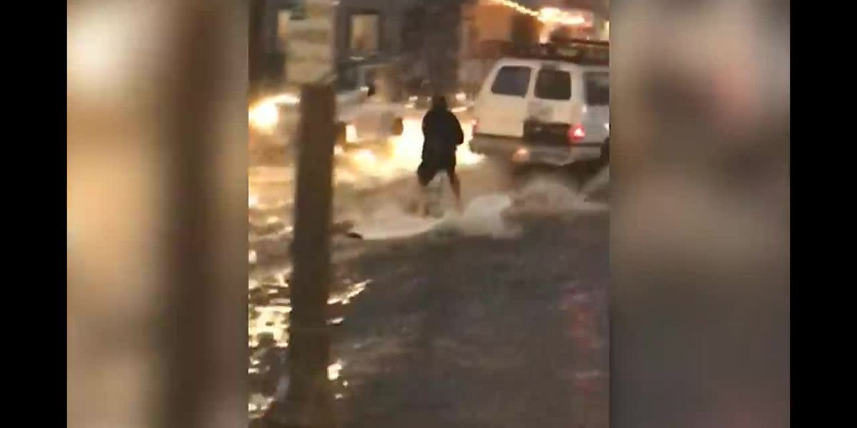 Man surfs on flooded roadway in San Diego County
