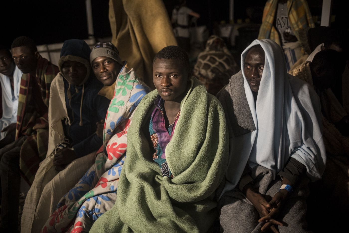 Vafin, 16, centre, from Guinea Conarky, sits with other migrants on the deck of Open Arms vessel, after they were rescued by the Spanish NGO Pro Activa Open Arms, about 40 miles (64 kms) from the Spanish coasts, on Thursday, Oct. 11, 2018. The Open Arms is now based at Motril port in order to start operating in the western Mediterranean area. (AP Photo/Javier Fergo)
