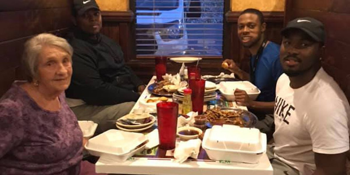 Men invite elderly woman to eat with them when they see her dining alone